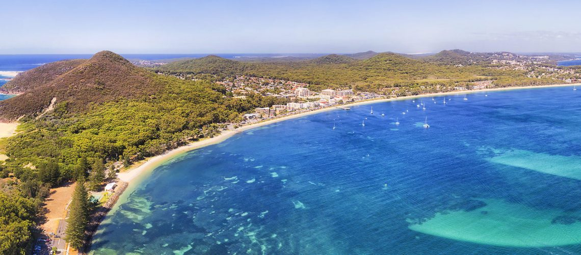 Port Stephens coast Shoal bay town waterfront with Mt Tomaree and Zenith beach in wide aerial panorama over water surface in Australia on a sunny day.